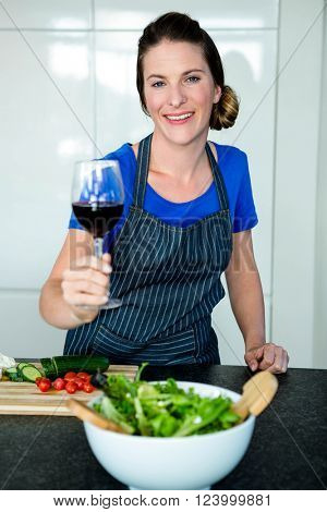 smiling woman in the kitchen, preparing vegetables and drinking red wine