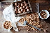 Постер, плакат: Walnut Kernels And Whole Walnuts On Rustic Old Wooden Table Who