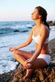stock photo of woman beach  - Woman meditating on the beach at sunset - JPG