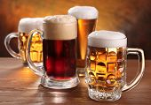 image of beer mug  - Cool beer mugs over wooden table - JPG