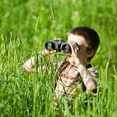 foto of boy scout  - Young boy in a field looking through binoculars - JPG