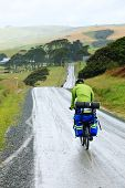 Cycle tourists on a dirt road in New Zealand poster