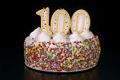 foto of centenarian  - a colorful birthday cake with candles shaped like the number 100 - JPG