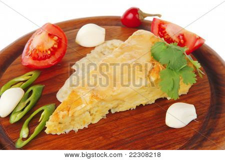dairy food : cheese casserole piece over wood plate served with peppers , tomatoes and chives isolated over white background