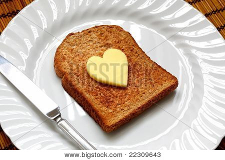 Healthy eating concept - piece of whole wheat toast on a white plate with a heart shaped symbol of butter
