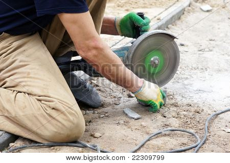 The worker cuts a stone the electric tool