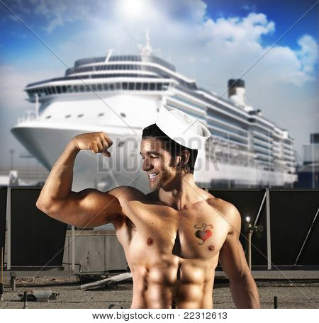 Sexy male model as sailor flexing his bicep in front of ship at port with a heart tattoo on his chest