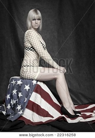 Young attractive pin up girl dressed in net lingerie sitting on american flag. Vintage style studio shot.