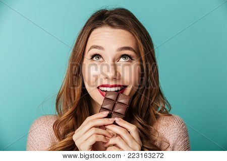 poster of Portrait of a delighted brown haired woman with bright makeup eating chocolate bar isolated over blu