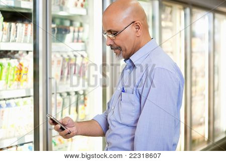 Smiling mature man looking at mobile phone while standing in front of refrigerator in supermarket