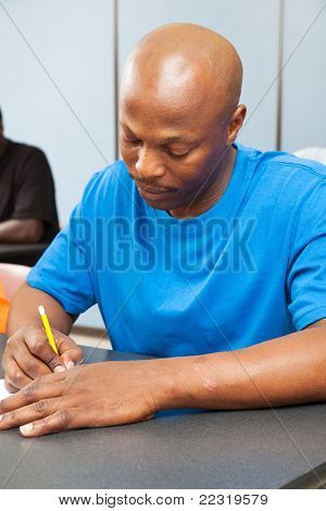 Handsome african-american college student taking a test.