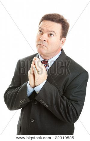 Christian businessman praying, looking upwards.  Isolated on white.