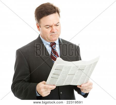 Businessman reading bad news in the newspaper.  Could be financial or political news.  Isolated on white.