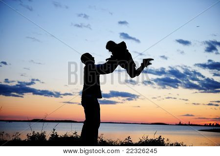Silhouette of father and daughter in the sunset