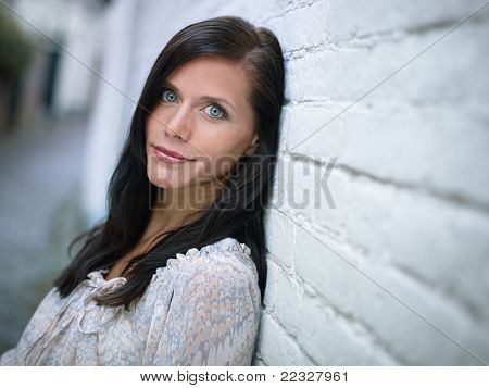 Attractive Girl Leaning On Wall And Smiling
