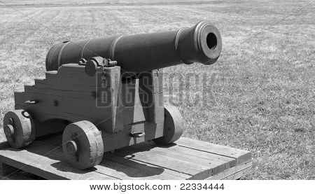 Black and white image an old small cannon on a grass field
