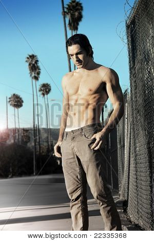 Fashion portrait of a young male model shirtless outdoors in urban setting