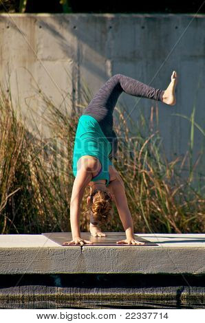Woman Doing Yoga Outdoors In Three Leg Downward Facing Dog Pose