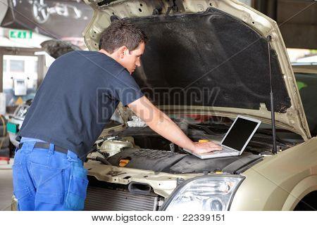 Mechanic using laptop while repairing car in garage