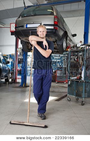 Full length portrait of young man leaning on broom in garage