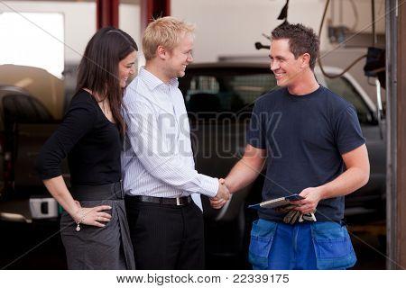 Glücklich attraktive Mechaniker Händeschütteln mit wenigen Kunden zufrieden mit ihrem service