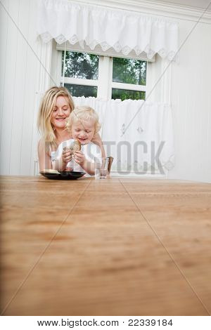 Smiling young mother with baby boy looking at bread at dining table