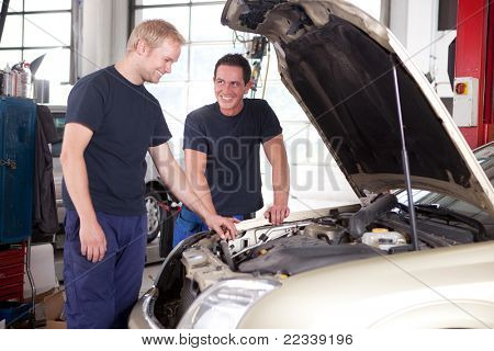 Two mechanics looking at and working on a car in a repair shop