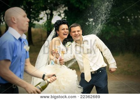 Young man opens sparkling wine and  splashing on wedding