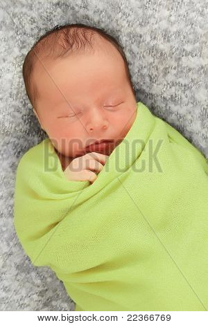 Newborn baby boy asleep wrapped in a green blanket.