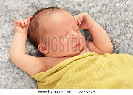 Newborn baby boy asleep wrapped in a yellow blanket.
