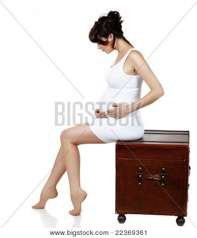 beautiful eight months pregnant brunette woman wearing white tight dress and sitting on antique chest over white background.