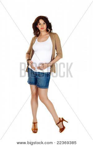 mooie acht maanden zwangere brunette vrouw mode shorts en hoge hakken dragen over witte stud