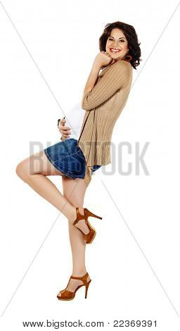 beautiful eight months pregnant brunette woman wearing fashion shorts and high heels over white studio background