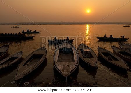 A stunning sunrise looking over the holiest of rivers in India. The Ganges. Silhouettes of boats dapple the horizon.