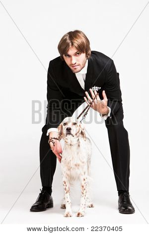 elegant young  man in tuxedo and his dog, studio shot