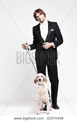 elegant young  man in tuxedo and his dog, studio shot