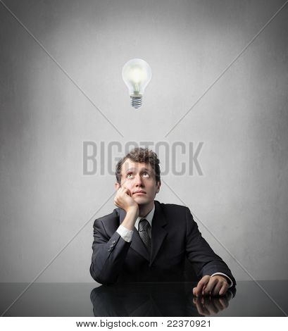 Businessman with thoughtful expression with light bulb over his head
