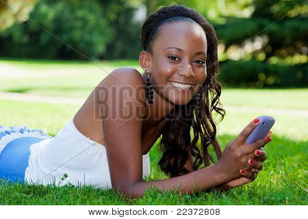 Teenage Black Girl Using A Cellphone, Lying On The Grass