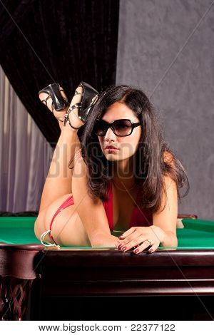 Attractive young brunette woman in sun glasses on a pool table