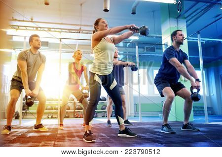 poster of sport, fitness, weightlifting and training concept - group of people with kettlebells exercising in