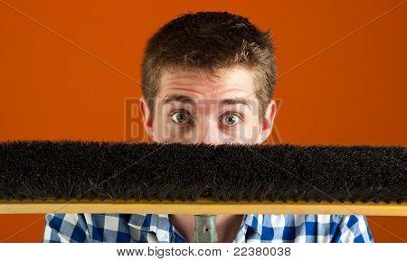Surprised Caucasian Male Hiding Behind Broom