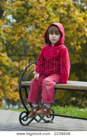 Kid Sitting On The Bench Outdoors