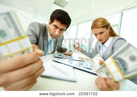 Image of angry employees with dollar bills in hands looking at you with aggression