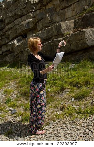 Woman Inspecting Rock.