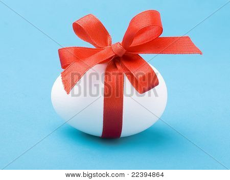 White egg wrapped around with red ribbon over blue background