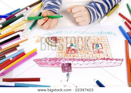 child drawing on paper with crayons