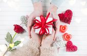Valentine Gift. Young Couple Hands holding gift box with red bow gift over wooden background. St. Va poster