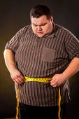 Man belly fat with tape measure weight loss around body on black background. First day of diet. Clot poster