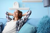 Young woman listening to music while relaxing on sofa at home poster