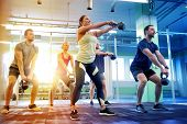 sport, fitness, weightlifting and training concept - group of people with kettlebells exercising in  poster